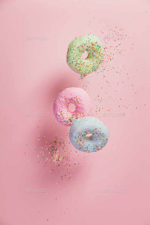 Sweet and colourful doughnuts with sprinkles falling or flying i - Stock Photo - Images