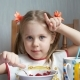 Little Girl Shows Her Fingers Like a Cow's Horns on Kitchen - VideoHive Item for Sale