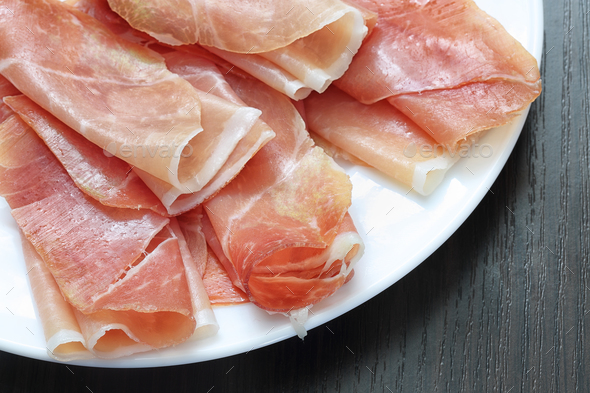 Sliced jamon (hamon) or prosciutto on a wooden background - Stock Photo - Images