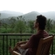 Man Relaxing on Balcony with Beautiful Mountain View on Vacation at the Hotel Apartment Terrace - VideoHive Item for Sale