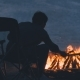 A Man Is Sitting in an Armchair Near Bright Fire on a Nightly Coast - VideoHive Item for Sale