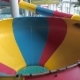 A Young Man Slides Down From a Water Slide in a Water Park People Ride From the Slides and Jump Into - VideoHive Item for Sale