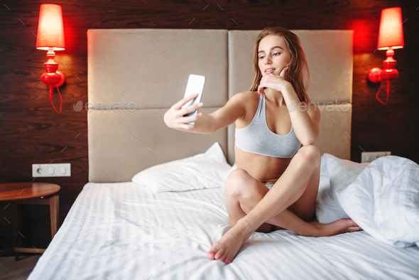 Pretty woman sitting in bed and makes selfie - Stock Photo - Images
