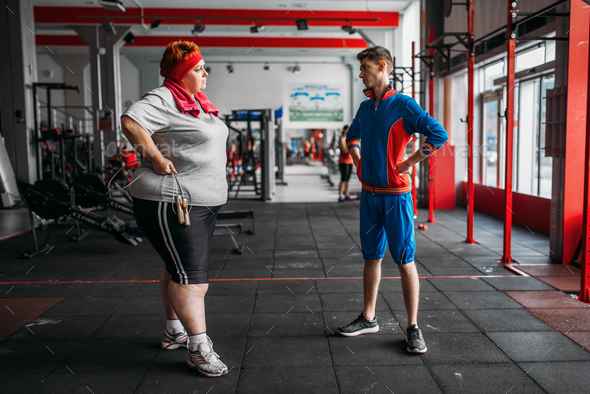 Fat woman talks with instructor after exercise - Stock Photo - Images
