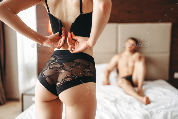 Sexy woman takes off underwear in front of a man - Stock Photo - Images