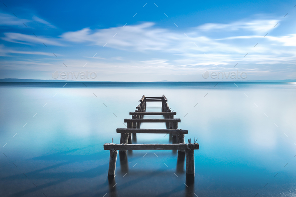 Wooden pier or jetty remains on a blue lake. Long Exposure. - Stock Photo - Images