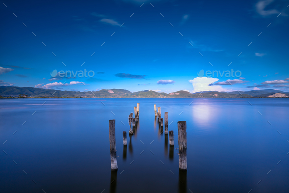 Wooden pier or jetty remains on a blue lake sunset and sky refle - Stock Photo - Images