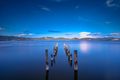Wooden pier or jetty remains on a blue lake sunset and sky refle - PhotoDune Item for Sale