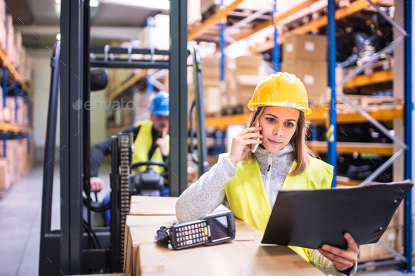 Warehouse workers with smartphone working together. - Stock Photo - Images