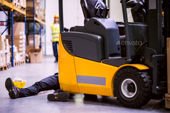 An injured worker after an accident in a warehouse. - Stock Photo - Images