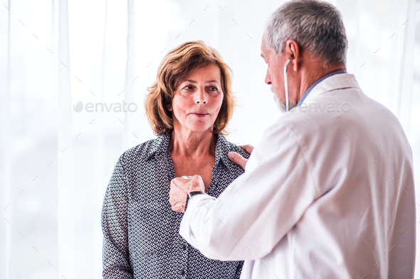 Male doctor examiming a senior woman in his office. - Stock Photo - Images