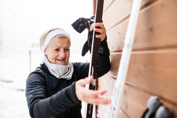 Senior woman getting ready for skiing. - Stock Photo - Images