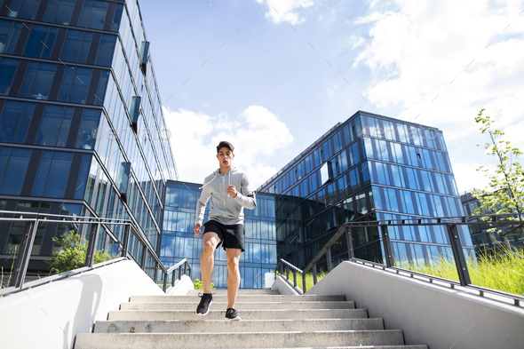 Young athlete running in front of glass buildings. - Stock Photo - Images