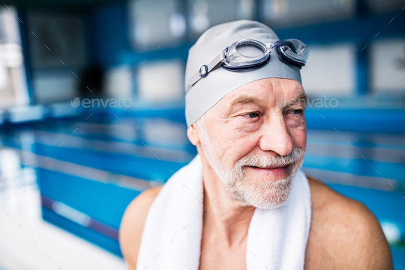 Senior man standing in an indoor swimming pool. - Stock Photo - Images