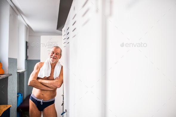Senior man standing by the lockers in an indoor swimming pool. - Stock Photo - Images