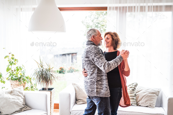 Senior couple relaxing at home, dancing. - Stock Photo - Images
