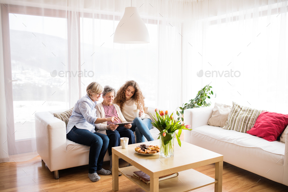 A teenage girl, mother and grandmother with tablet at home. - Stock Photo - Images