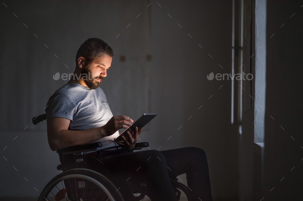 Man in wheelchair working with tablet. - Stock Photo - Images