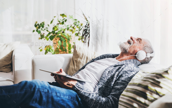 Senior man with tablet relaxing at home. - Stock Photo - Images