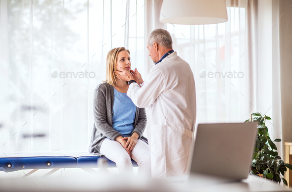 Senior doctor examining a young woman in office. - Stock Photo - Images