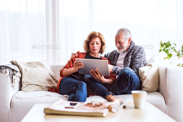 Senior couple with tablet relaxing at home. - Stock Photo - Images
