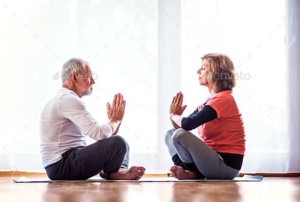 Senior couple meditating at home. - Stock Photo - Images