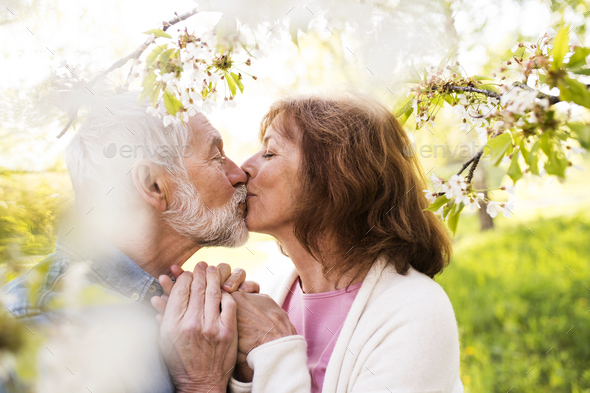 Senior couple in love outside in spring nature kissing. - Stock Photo - Images