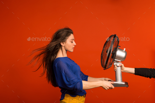 Portrait of a young beautiful woman with a fan in studio. - Stock Photo - Images