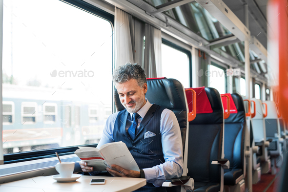 Mature businessman travelling by train. - Stock Photo - Images