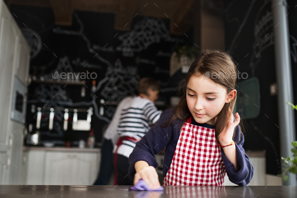 A small girl helping in the kitchen at home. - Stock Photo - Images