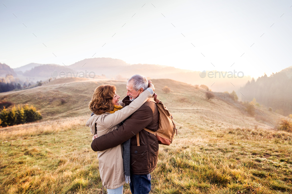 Senior couple on a walk in an autumn nature. - Stock Photo - Images
