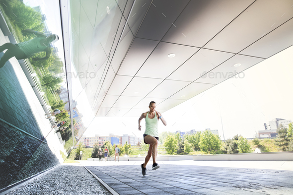 Beautiful young athlete running in the city. - Stock Photo - Images