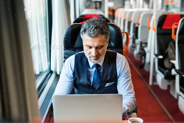Mature businessman with laptop travelling by train. - Stock Photo - Images