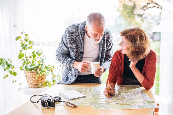 Senior couple with map at home, making plans. - Stock Photo - Images