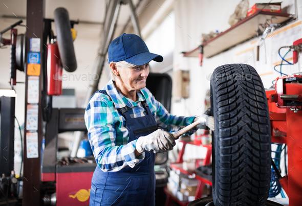 Senior female mechanic repairing a car in a garage. - Stock Photo - Images
