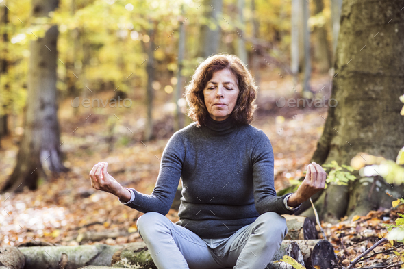 Senior woman meditating in an autumn forest. - Stock Photo - Images