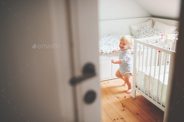 Cute toddler boy running in a bedroom. - Stock Photo - Images