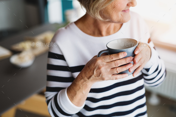 Senior woman holding a cup of coffee in the kitchen. - Stock Photo - Images