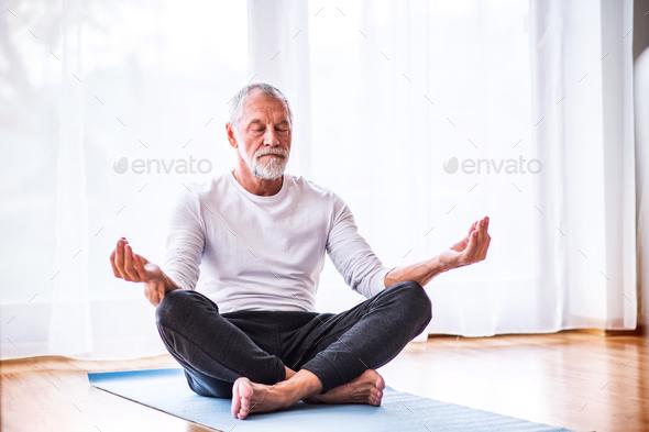 Senior man meditating at home. - Stock Photo - Images
