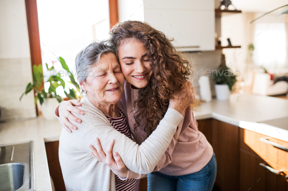 A teenage girl with grandmother at home, hugging. - Stock Photo - Images