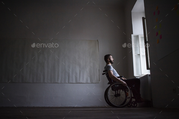 Man in wheelchair looking out of the window. - Stock Photo - Images