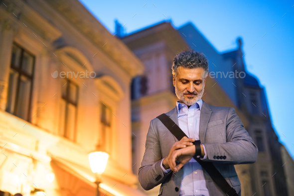 Mature businessman with a smartwatch in a city. - Stock Photo - Images