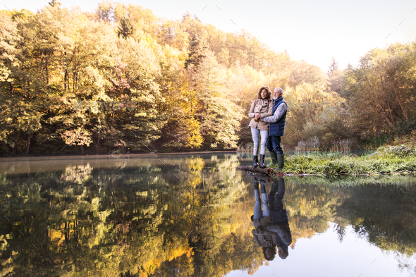 Senior couple on a walk in autumn nature. - Stock Photo - Images