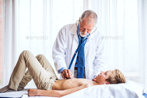 Senior doctor examining a small boy in his office. - Stock Photo - Images