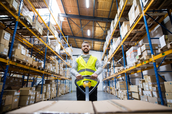 Male warehouse worker pulling a pallet truck. - Stock Photo - Images