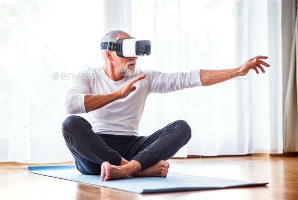 Senior man with VR goggles doing exercise at home. - Stock Photo - Images