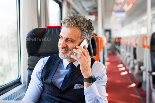 Mature businessman with smartphone travelling by train. - Stock Photo - Images