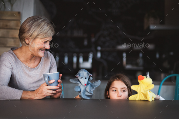 A small girl and grandmother with puppets at home. - Stock Photo - Images