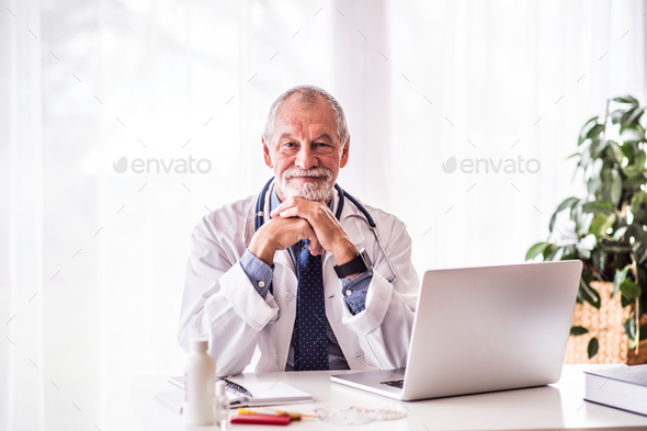 Senior doctor with laptop sitting at the office desk. - Stock Photo - Images