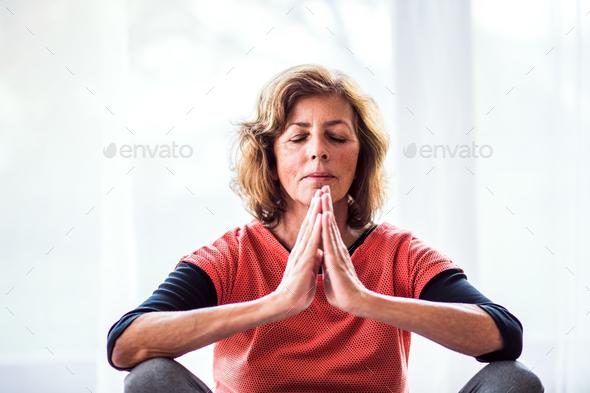Senior woman meditating at home. - Stock Photo - Images